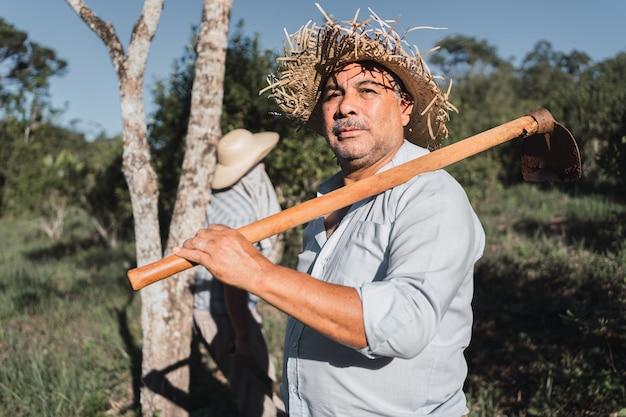 Retrato de um homem maduro trabalhando no solo com uma enxada.