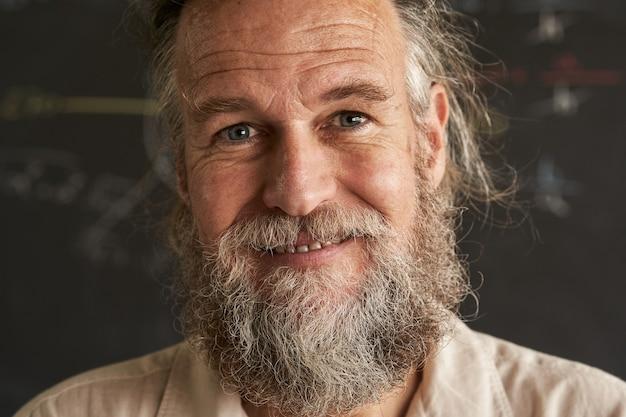 Retrato de um homem mais velho com barba e cabelos grisalhos o homem tem um sorriso amigável e sincero