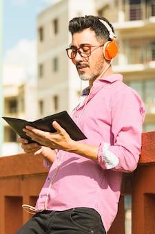 Retrato, de, um, homem moderno, ficar, contra, parede, escutar música, ligado, headphone, leitura, a, livro