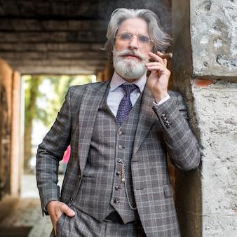 Retrato de um homem moderno fumando charuto cubano Foto gratuita