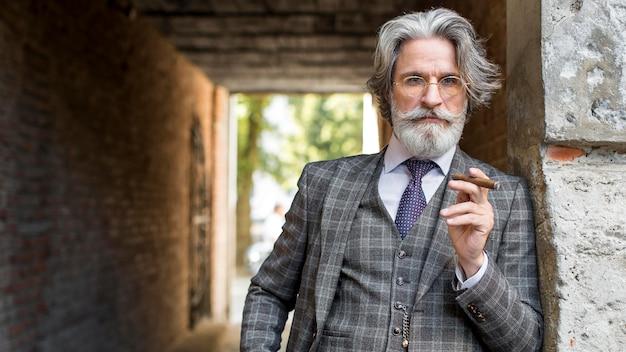 Retrato de um homem moderno fumando charuto cubano