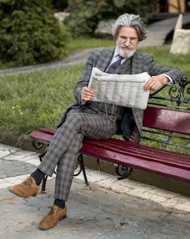 Retrato de um homem moderno lendo jornal em um banco