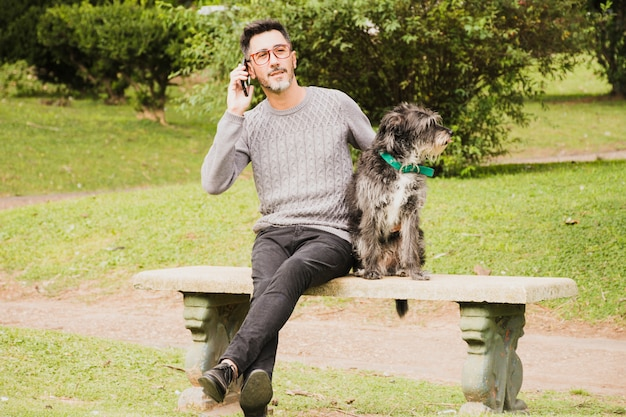 Retrato, de, um, homem moderno, sentando, parque, com, seu, cão, falando telefone móvel