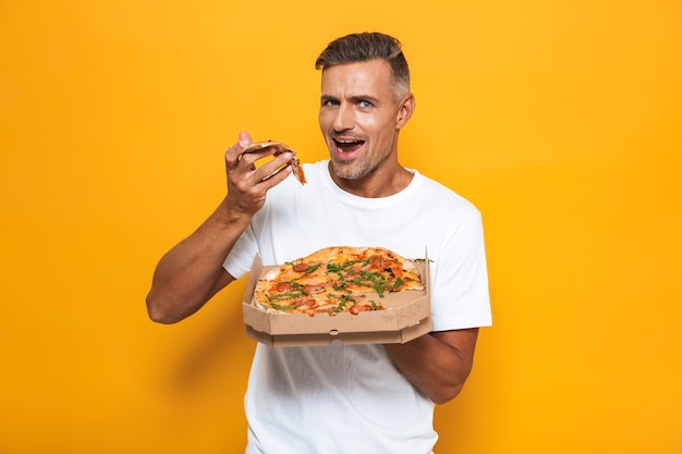 Retrato de um homem moreno de 30 anos em uma camiseta branca segurando e comendo pizza em pé isolado em amarelo