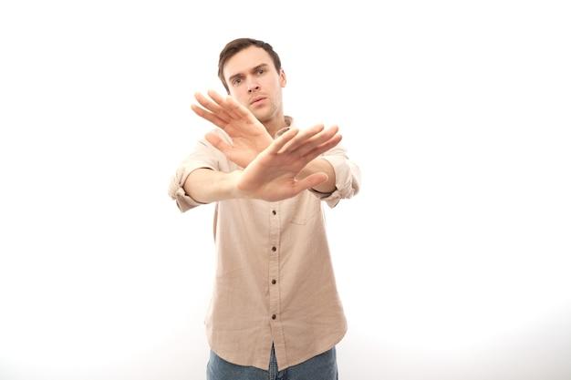Retrato de um homem moreno em casual mostrando um gesto de parada, não, por favor, você foi recusado, isolado no fundo branco do estúdio