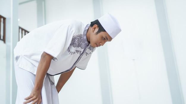 Retrato de um homem muçulmano asiático orando na mesquita, o nome da oração é sholat, movimento rukuk