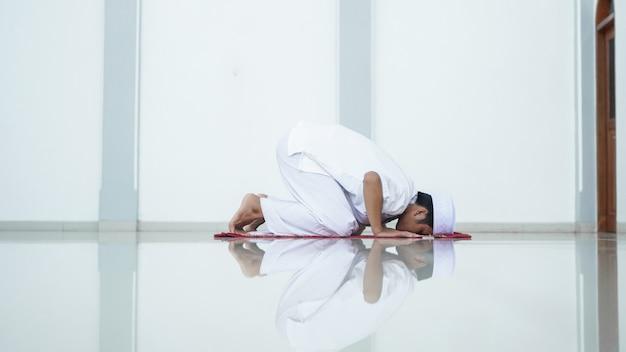 Retrato de um homem muçulmano asiático orar na mesquita, o nome da oração é sholat, movimento sujud no sholat