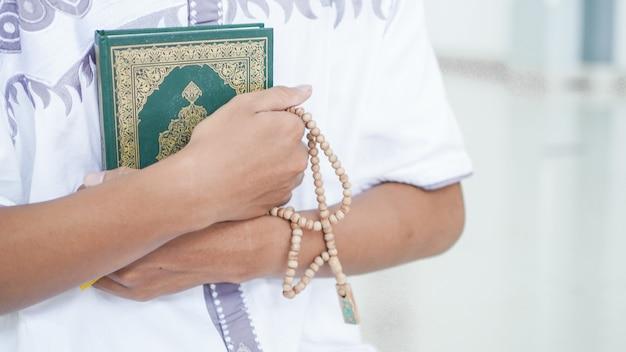 Retrato de um homem muçulmano asiático segurando alcorão e tasbih