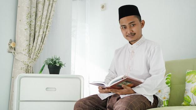 Retrato de um homem muçulmano asiático sentado no sofá lendo o alcorão em casa