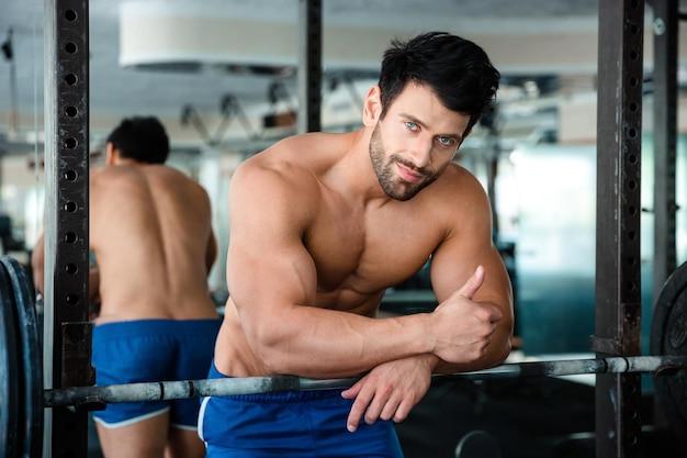 Retrato de um homem musculoso bonito aparecendo o polegar no ginásio de fitness