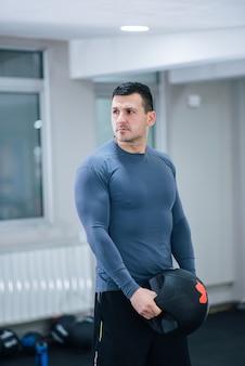 Retrato de um homem musculoso bonito exercitando com bola de medicina de pesos.