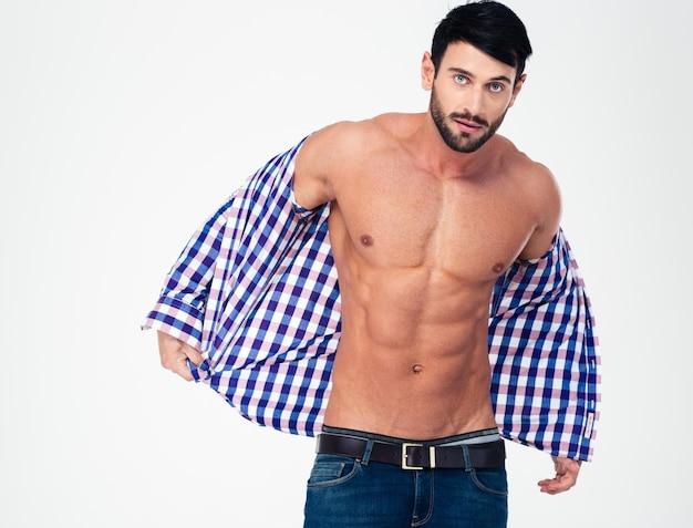 Retrato de um homem musculoso bonito tirando a camisa isolada em uma parede branca