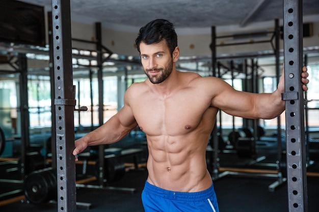 Retrato de um homem musculoso descansando em uma academia de ginástica