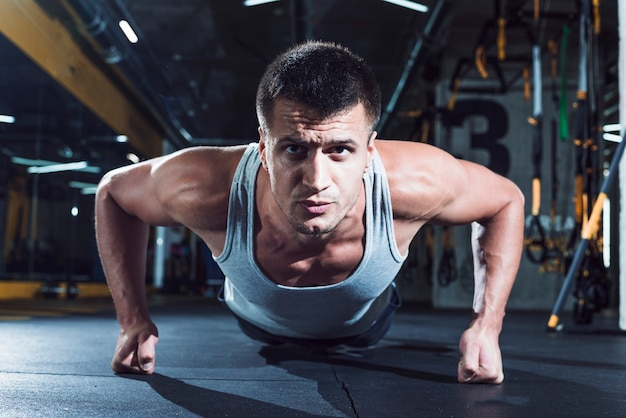 Retrato de um homem musculoso fazendo push ups no ginásio