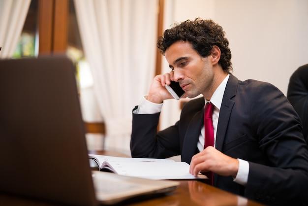 Retrato, de, um, homem negócios, conversa telefone, em, seu, escritório