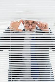 Retrato, de, um, homem negócios, espreitar, através, cortinas, em, escritório