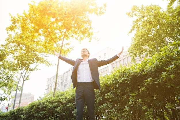 Retrato, de, um, homem negócios fica, frente, predios, levantando, seu, braços