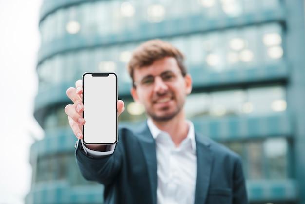 Retrato, de, um, homem negócios fica, frente, predios, mostrando, telefone móvel