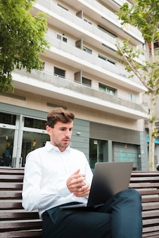 Retrato, de, um, homem negócios, olhar, seriamente, em, laptop, frente, predios