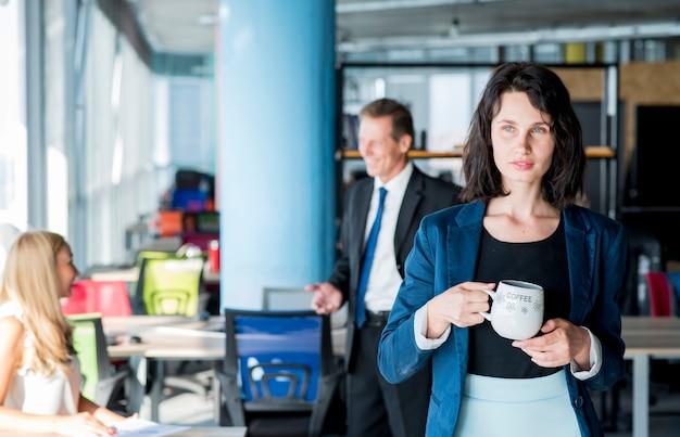 Retrato, de, um, homem negócios, segurando, xícara café, em, escritório
