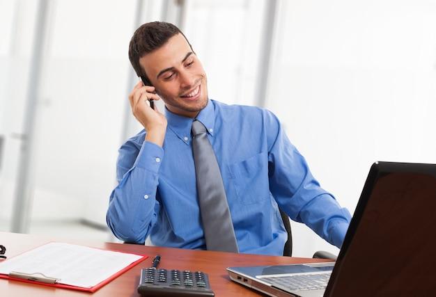 Retrato, de, um, homem negócios, usando, seu, laptop, enquanto, conversa telefone
