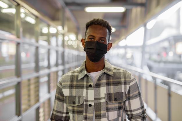 Retrato de um homem negro africano ao ar livre na cidade durante o verão usando máscara facial