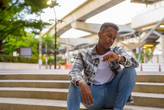 Retrato de um homem negro africano ao ar livre na cidade durante o verão, verificando o tempo no disparo horizontal do relógio de pulso