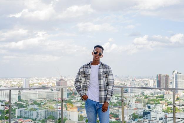 Retrato de um homem negro africano ao ar livre na cidade no telhado durante o verão horizontal.
