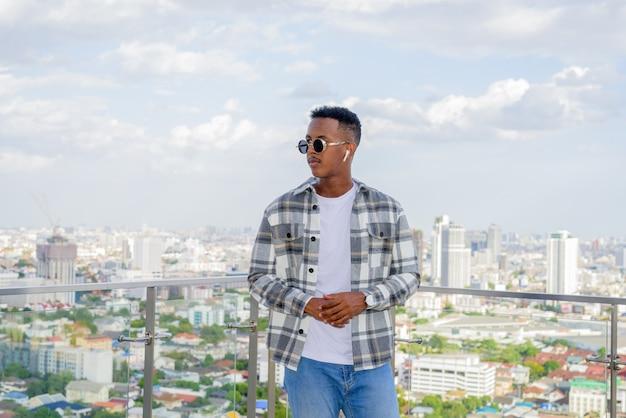 Retrato de um homem negro africano ao ar livre na cidade no telhado durante o verão usando óculos escuros e pensando