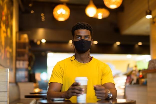 Retrato de um homem negro africano bonito vestindo uma camiseta amarela ao ar livre na cidade de bangkok, tailândia
