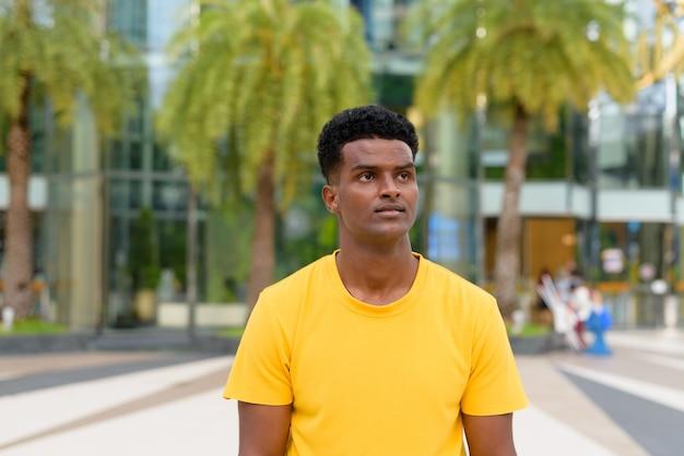 Retrato de um homem negro africano bonito vestindo uma camiseta amarela ao ar livre na cidade durante o verão enquanto pensa