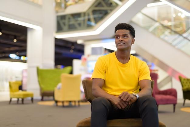 Retrato de um homem negro africano bonito vestindo uma camiseta amarela enquanto está sentado e pensando