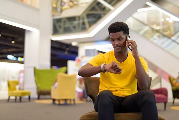 Retrato de um homem negro africano bonito vestindo uma camiseta amarela enquanto está sentado e verificando o relógio de pulso enquanto fala ao telefone