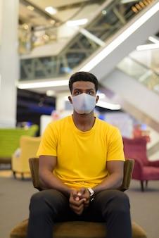 Retrato de um homem negro africano bonito vestindo uma camiseta amarela enquanto usa uma máscara facial para se proteger do coronavírus covid-19