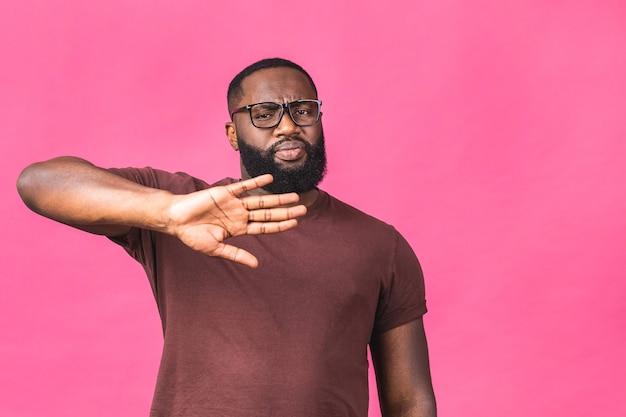 Retrato de um homem negro afro-americano, segurando a mão em sinal de stop, avisando e impedindo você de algo ruim, olhando para a câmera com expressão preocupada isolada sobre fundo rosa.