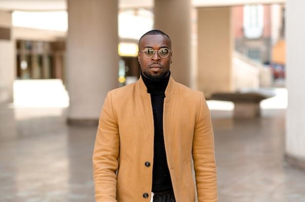 Retrato de um homem negro atraente com cara séria, olhando para a câmera. cara barbudo com óculos de sol em roupas elegantes e elegantes.