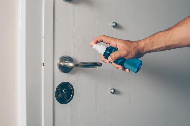 Retrato de um homem no quarto higienizando o manipulador da porta.