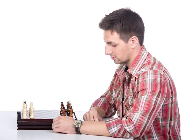 Retrato de um homem novo bonito na tabela com xadrez.
