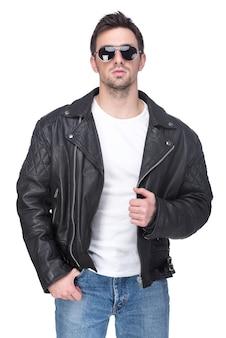 Retrato de um homem novo em uma jaqueta de couro e óculos de sol.