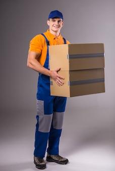 Retrato de um homem novo na roupa de trabalho com caixas.