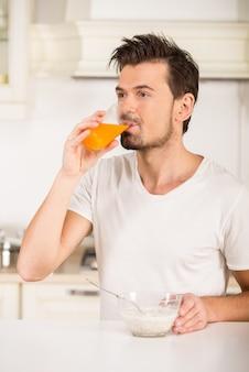 Retrato de um homem novo que esteja bebendo o suco na cozinha.