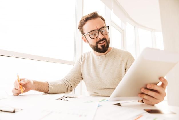 Retrato de um homem ocupado trabalhando com documentos