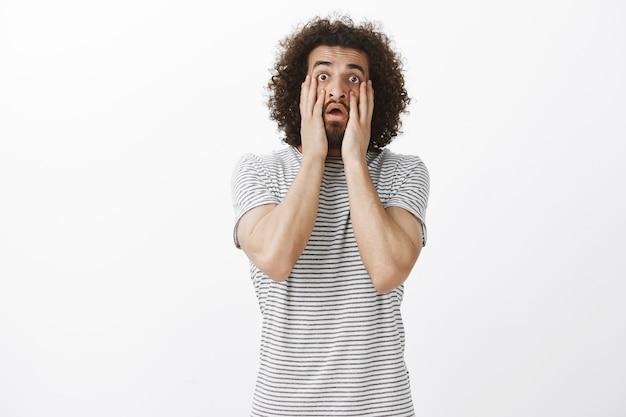 Retrato de um homem oriental chocado e farto de barba e cabelo afro, segurando as mãos no rosto e puxando as pálpebras, entediado e cansado