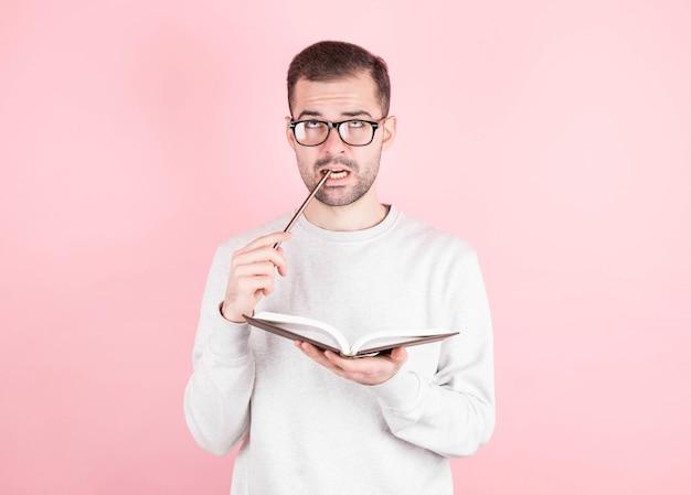 Retrato de um homem pensativo com um caderno e um lápis na boca em rosa