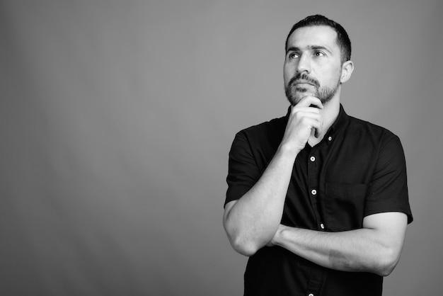 Retrato de um homem persa barbudo bonito vestindo uma camisa preta cinza em preto e branco