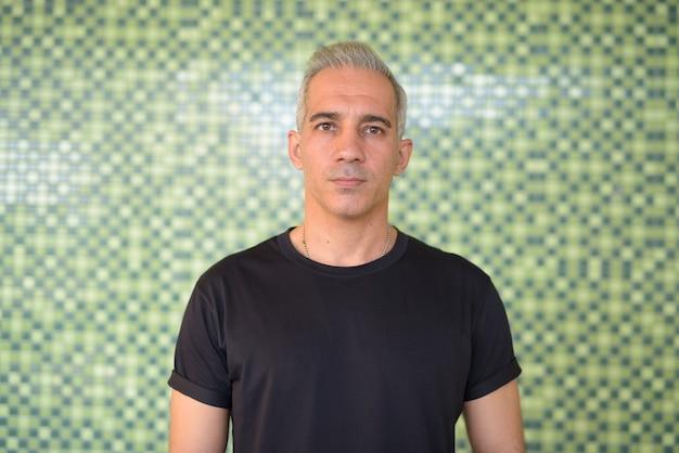 Retrato de um homem persa bonito com cabelo grisalho contra uma parede verde ao ar livre