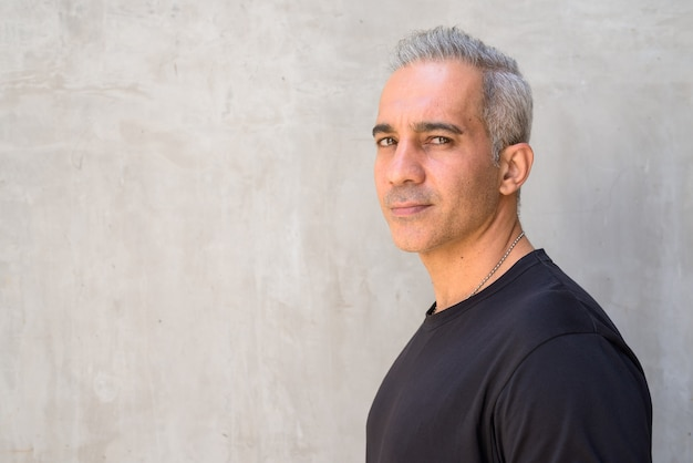Retrato de um homem persa bonito com cabelos grisalhos contra uma parede de concreto ao ar livre