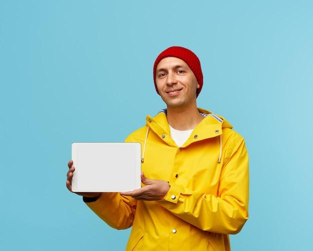 Retrato de um homem positivo e legal mostrando a tela branca do tablet