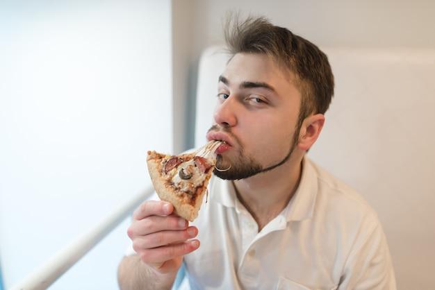 Retrato de um homem que come um pedaço de pizza e olha para a câmera. um homem com barba gosta do sabor da pizza quente