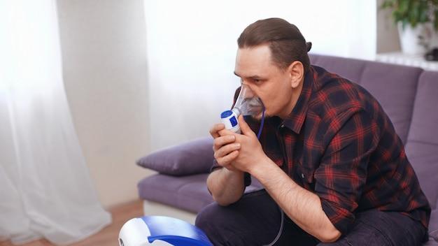 Retrato de um homem que respira através de uma máscara de inalador em casa.